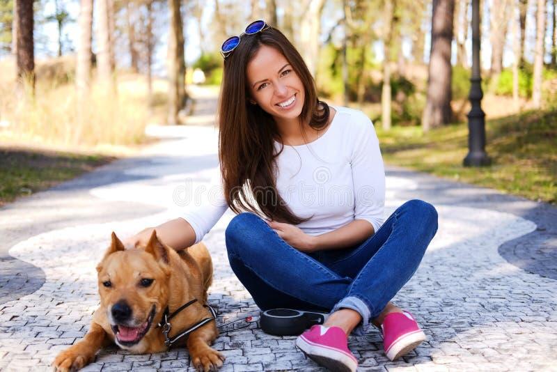 Outdoors stylu życia portret piękna dziewczyna z ślicznym psem si fotografia royalty free