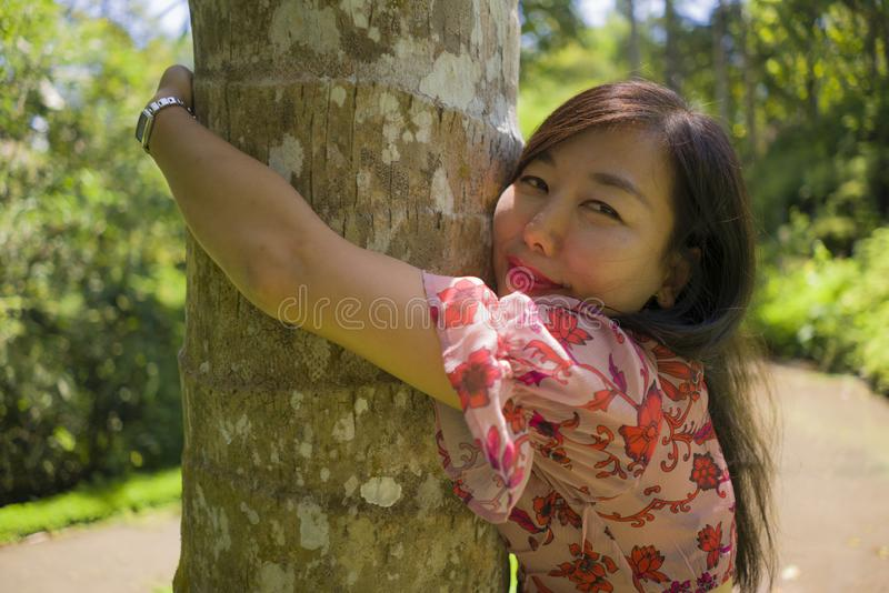 Summer lifestyle portrait of young beautiful and playful Asian Korean woman climbing and hugging tree trunk and tropical wood royalty free stock photo