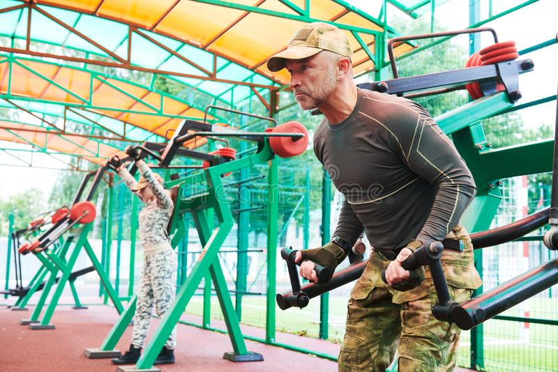 Outdoors training. man and woman workouts on weight machine in military clothing. Man and women in military clothing training outdoors on weight machine royalty free stock photos