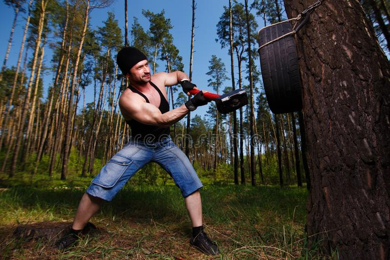 Strong healthy adult ripped man with big muscles hitting car tyr stock image