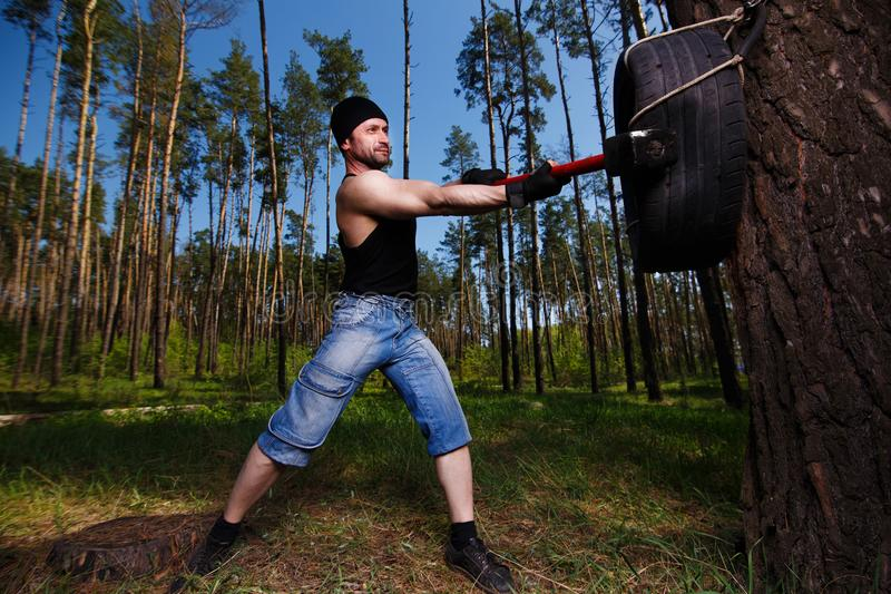 Strong healthy adult ripped man with big muscles hitting car tyr royalty free stock image