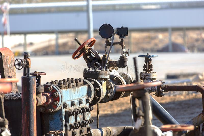 Different types of valves and indicators in the oil industry. Outdoors worn and active pipe valve system used in oil industry royalty free stock photo