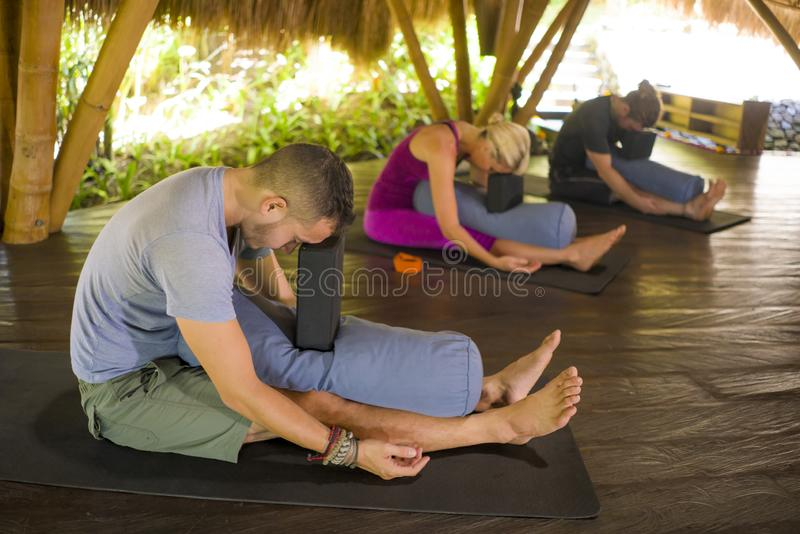Outdoors yoga lesson - group of young people and coach woman practicing relaxation exercise at Asian wellness retreat hut training stock image