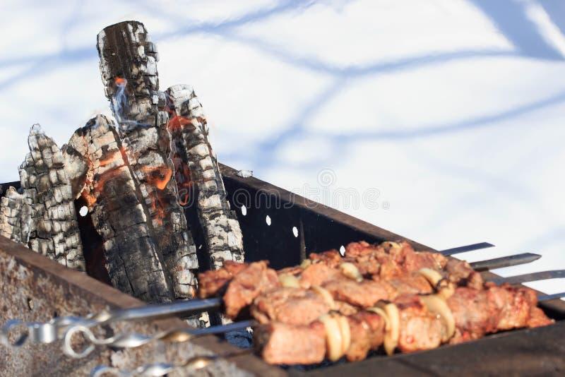 Outdoors zima grilla przyjęcie gotuje mięso z osobą jest ubranym trykotowe włóczkowe rękawiczki obrazy stock