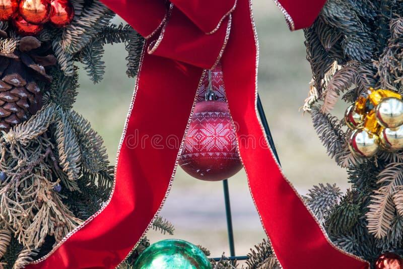 Outdoors zima wakacje dekoracji pojęcie: Naturalny Bożenarodzeniowy wianek z Czerwonym faborkiem i Kolorowymi piłkami dekoruje bu fotografia royalty free
