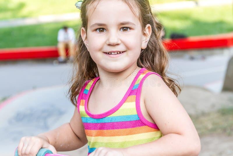 Outdor-Porträt des jungen lächelnden Mädchenreitrollers lizenzfreies stockbild