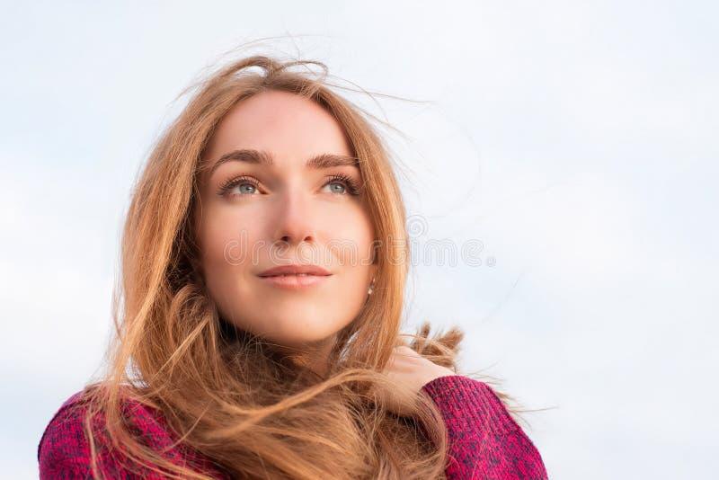 Outdor stående av den fridfulla härliga kvinnan med långt hårfladdrande arkivbild