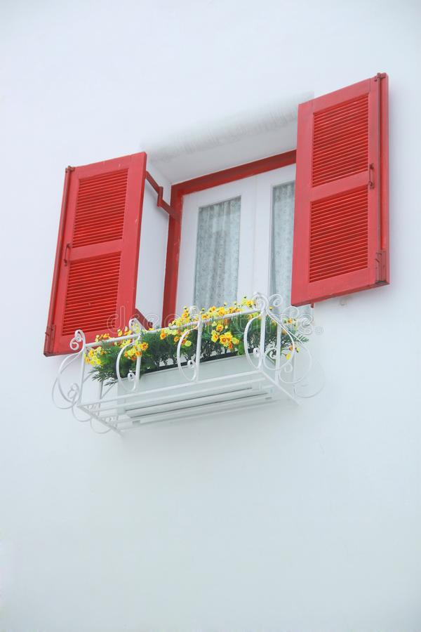 Outer opened red and white inner closed window with white wall decorated with flowerpod stock image