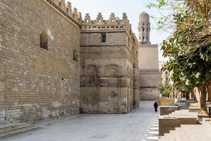 Outer wall and minaret of public historic Al Hakim Mosque - Enlightened Mosque - Moez Street, Cairo. Cairo, Egypt- March 21 2015: Outer wall of public historic stock photo