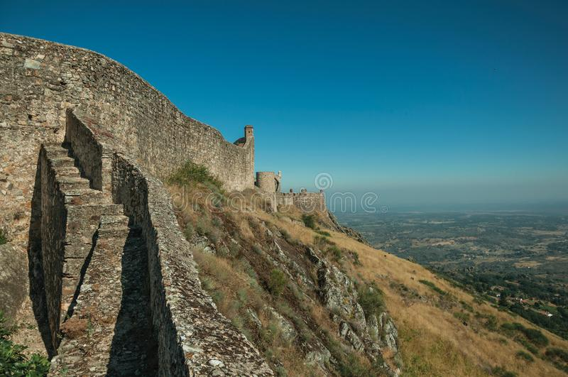 Outer walls and towers over rocky hill at the Marvao Castle. Stone outer walls and towers over rocky hill with countryside landscape, in a sunny day at the stock photos