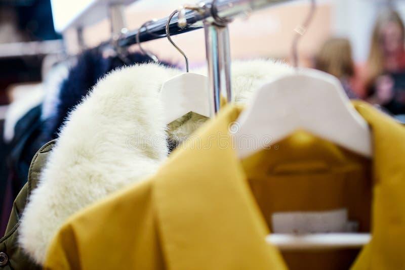 Outerwear на вешалках с людьми на заднем плане стоковое фото