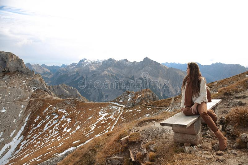 Outfit of casual woman. Brunette sitting on bench enjoying nature above mountains view landscape. Travel Lifestyle adventure. Vacations outdoor. Girl wearing stock photography