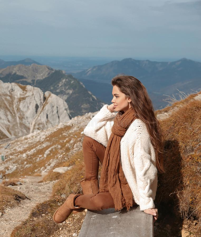 Outfit of casual woman. Brunette sitting on bench enjoying nature above mountains view landscape. Travel Lifestyle outdoor look s. Tyle. Girl wearing fashion royalty free stock image