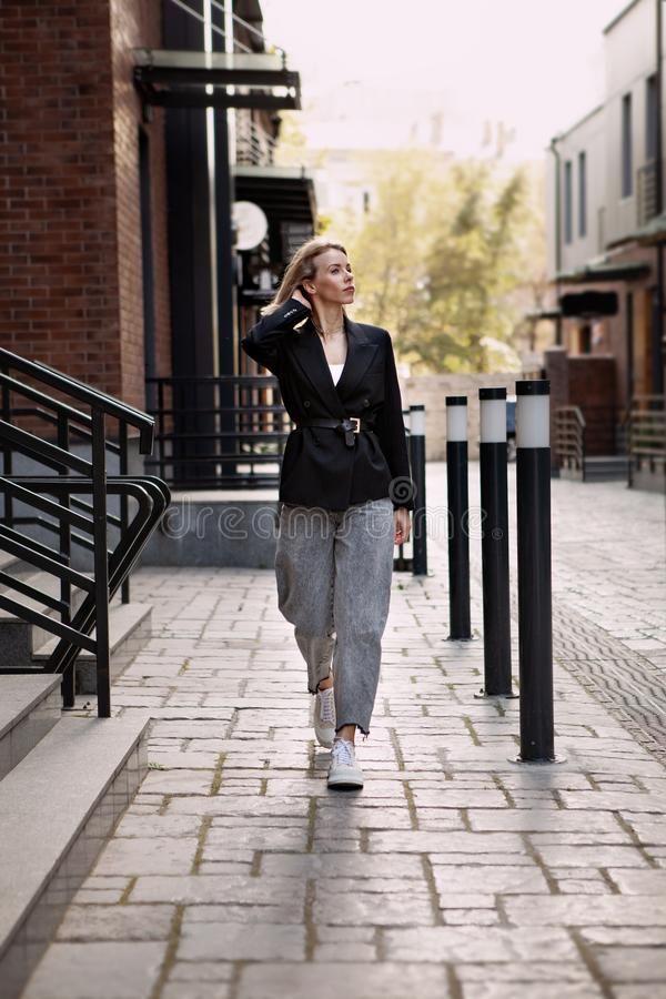 Outfit fashion, young stylish businesswoman wearing oversized black jacket, grey jeans and trendy white sneakers. Outfit fashion clothing, young stylish woman stock photo