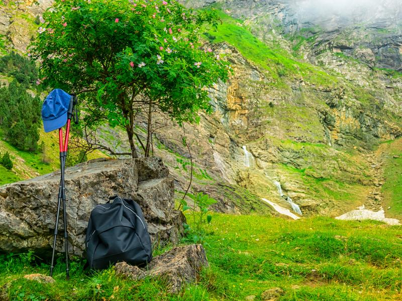 Outfit hiker. Backpacks, walking sticks and a tourist`s cap in the mountains on a halt under a tree royalty free stock images