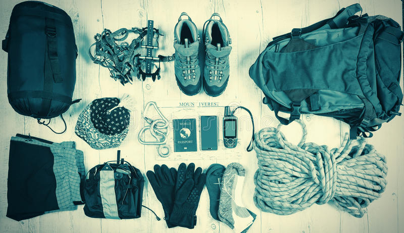 Outfit of traveler, climber, student, teenager. Overhead of essentials for modern sport young person. Different objects on wooden royalty free stock photo
