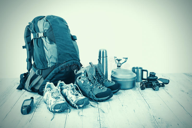 Outfit of traveler, climber, student, teenager. Overhead of essentials for modern sport young person. Different objects on wooden stock photography