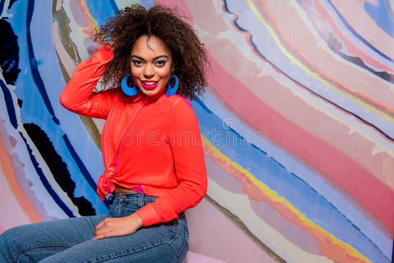 Outgoing african female locating in room. Beaming mulatto woman with bright makeup situating near colorful wallpaper. Copy space in right side royalty free stock photos