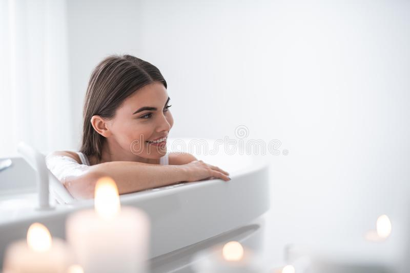 Outgoing female having leisure in foam water. Portrait of happy pretty woman with attractive smile relaxing while taking bath in bright apartment during romantic royalty free stock images