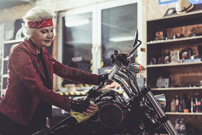 Outgoing pensioner burnishing bike in mechanic shop. Cheerful female retiree rubbing motorcycle in comfortable mechanic shop stock images