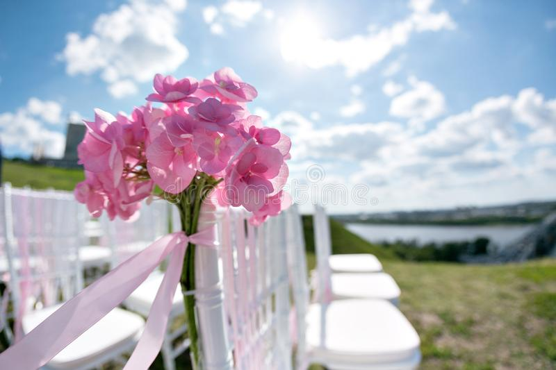 Tapes fly in the wind. Romantic wedding ceremony. White wooden chairs with ribbon and flowers on a green lawn. Nice stock image