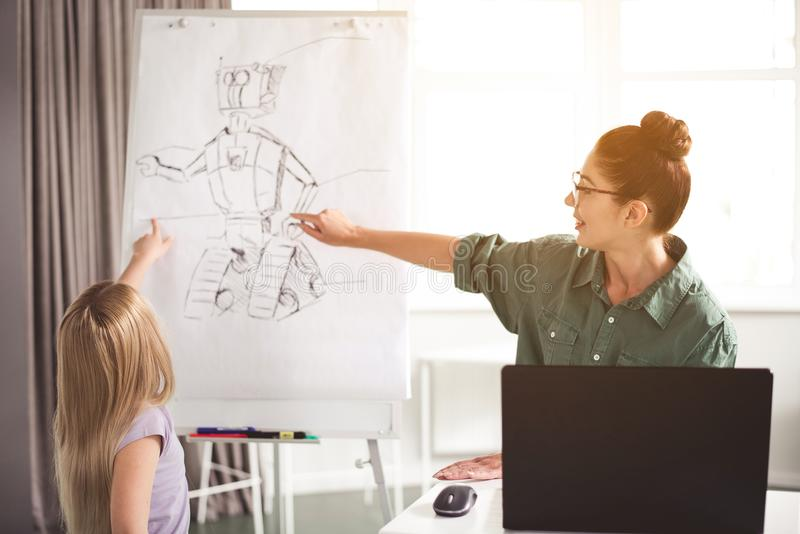 Cheerful teacher and kid showing on image of robot royalty free stock image
