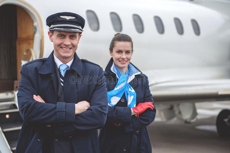 Outgoing workers standing near aircraft stock images