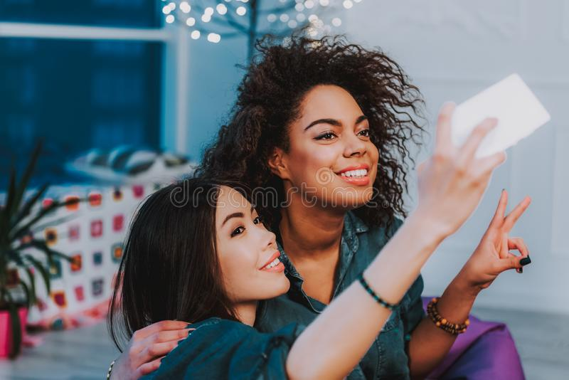 Outgoing young girls taking photo by mobile royalty free stock photos