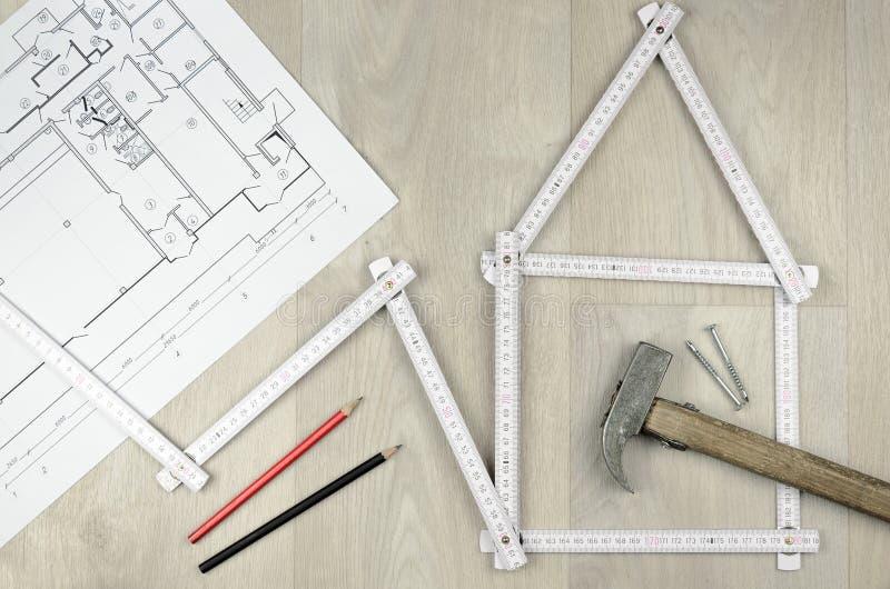 Outil blanc de mètre formant une maison et machinant des outils sur le woode photo stock