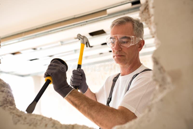 Outil de fixation de travailleur de la construction et cloison sèche de fracas photographie stock