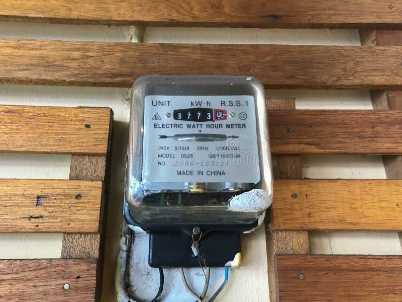 Outil de mesure de mètre électrique de watt-heure sur le mur en bois photo libre de droits