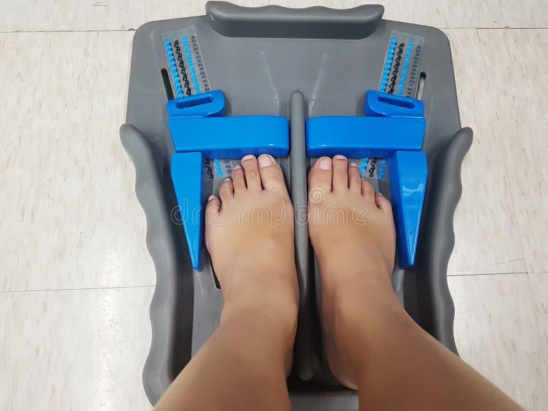 Outil de mesure de pied - pieds de client dans la taille de chaussure de mesure photographie stock