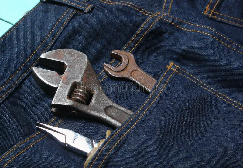 Outil de travail dans la poche arrière des jeans Pinces, clé, clé réglable photographie stock libre de droits