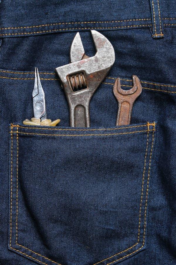 Outil de travail dans la poche arrière des jeans Pinces, clé, clé réglable photo stock