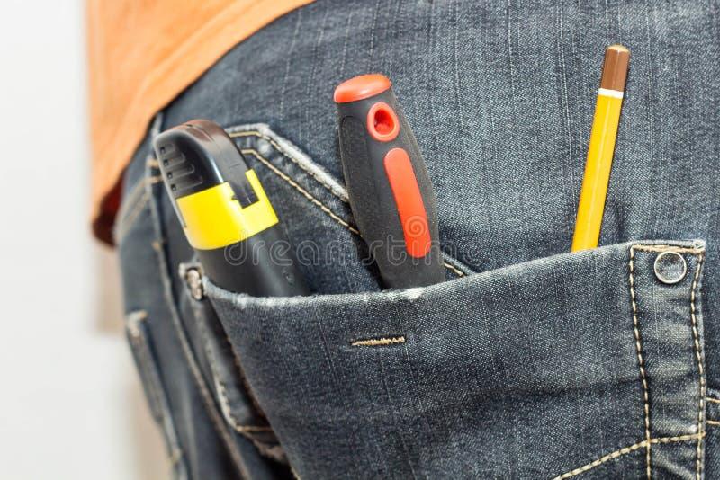 Outil de travaux d'ingénierie dans la poche arrière des jeans marteau de tournevis de crayon et couteau de service image stock