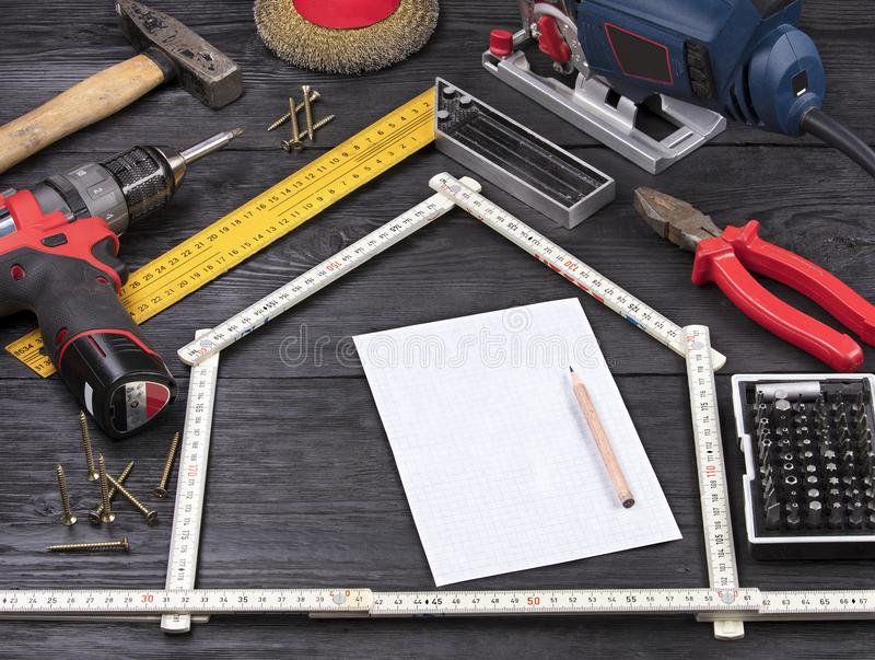 Outil pour la construction et la réparation sur un fond en bois noir autour d'une feuille de papier blanche avec un crayon photographie stock libre de droits
