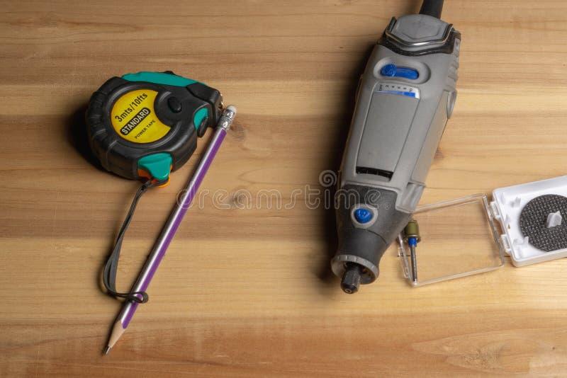 Outil rotatoire, ruban métrique et crayon de perceuse sur le blanc de meubles image libre de droits