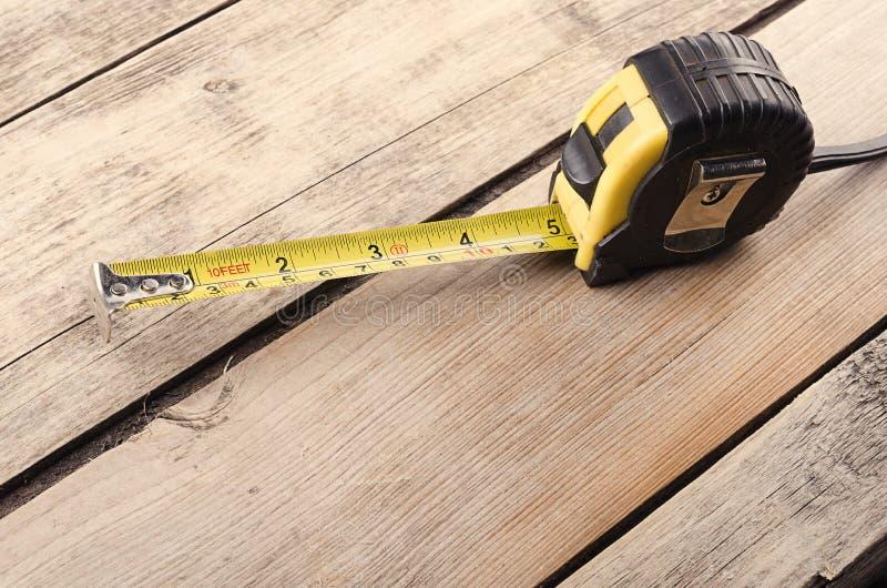 Outils Attachez du ruban adhésif à la mesureuse sur le fond en bois Préparez pour le travail photographie stock libre de droits