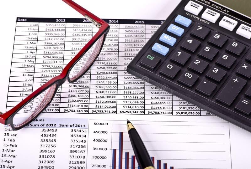 Outils, calculatrice, stylo et Spéc. financiers au-dessus d'un rapport images stock