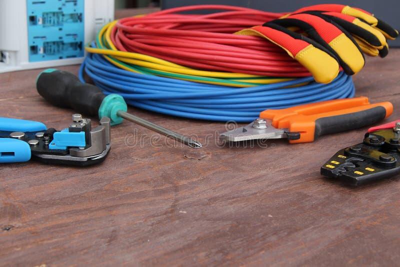 Outils d'électricien avec le fil rouge et bleu présenté sur une surface en bois de couleur foncée photographie stock libre de droits