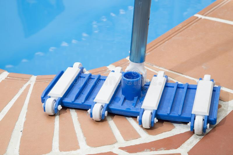 Outils d'entretien d'écumoire de brosse et de feuille de mur sur la plate-forme près de la piscine photographie stock libre de droits