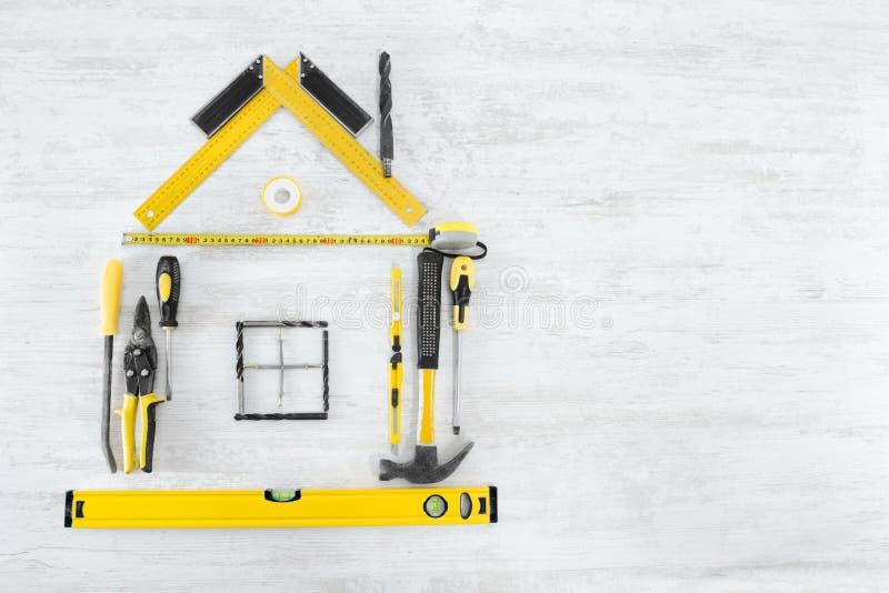 Outils dans la forme de la maison. Fond en bois photographie stock