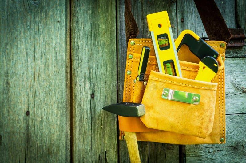 Outils dans le sac pour le travail sur le vieux fond en bois photographie stock