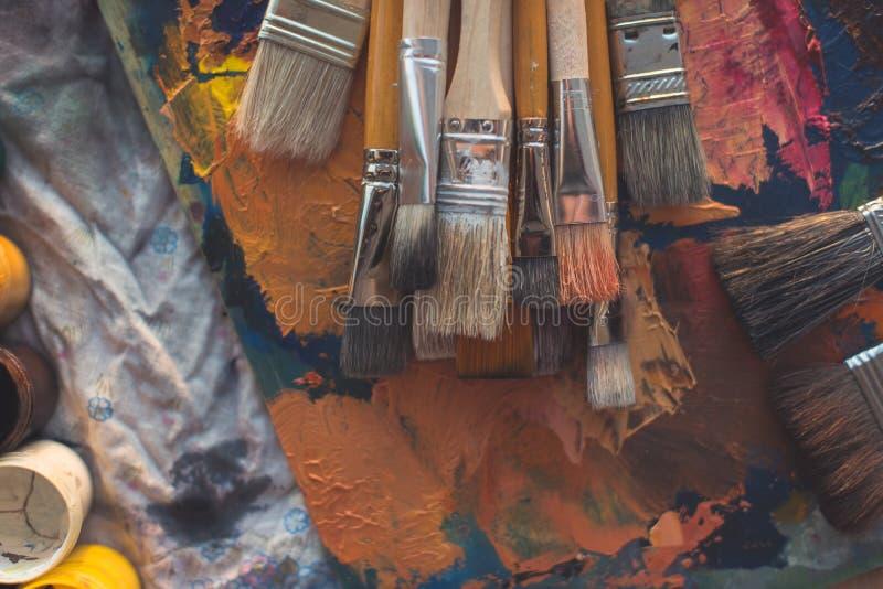 Outils de classes de dessin dans le studio d'art Photo de vue d'angle des pinceaux se trouvant sur des traçages de peintures à l' images stock