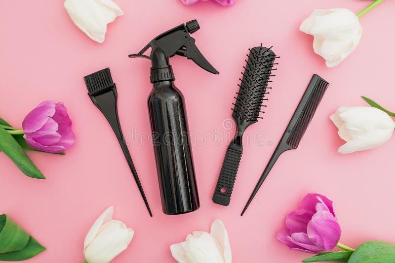 Outils de coiffeur - jet, peignes et fleurs de tulipes sur le fond rose Concept de beauté Configuration plate, vue supérieure images stock