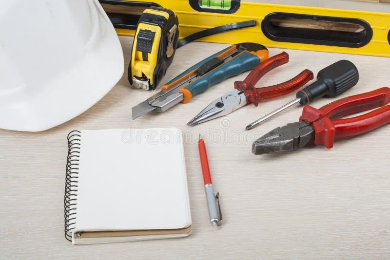 Outils de construction et casque blanc sur le fond en bois photo libre de droits