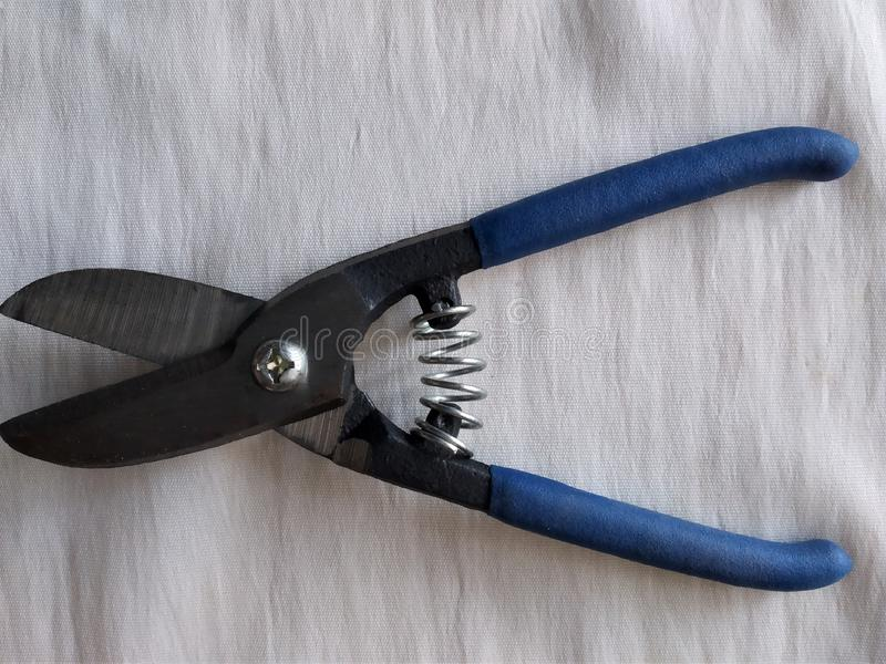 Outils de construction, petits ciseaux pour la coupe en métal, un fond blanc photographie stock libre de droits