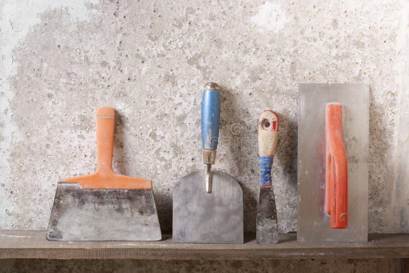 Outils de construction sur le fond concret Copiez l'espace pour le texte Ensemble de truelle et de spatule assorties de plâtre images stock