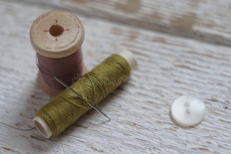 Outils de couture sur le fond en bois blanc Foyer serré et trouble photo stock