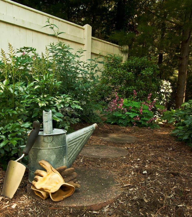 Outils de jardin dans le jardin de régfion boisée images libres de droits